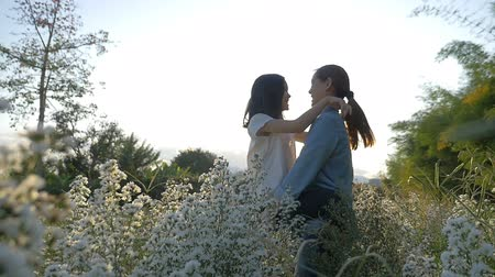 asian family : Slow motion of Happy Asian girl kissing her mother in the flower field with sunlight Stock Footage