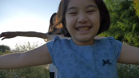 asian family : Slow motion of Happy Asian girl walking with her sister in the flower field with sunlight
