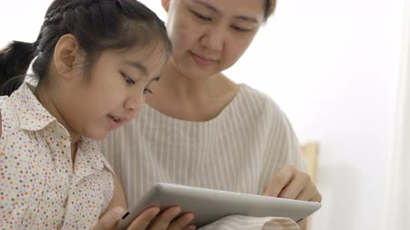 gry komputerowe : 4K : Happy Asian girl playing digital tablet with her mother