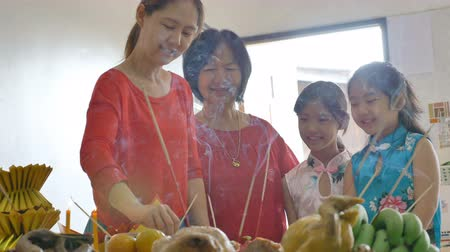 famílias : 4K : Happy Asian Family praying for a prosperous in Chinese New Year Celebrations Stock Footage