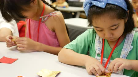 társult : 4K : Asian child learning to folding Japanese paper origami, art of paper folding, which is often associated with Japanese culture.