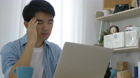 uncomfortable : 4K Young Asian businessman working on laptop at office, feeling tired and having headache