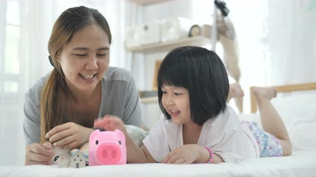 piggy bank : Slow motion 4K Lovely little Asian girl and mother putting money in piggy bank for saving