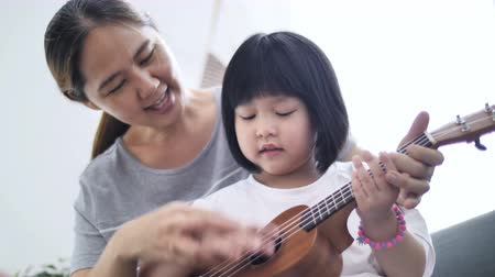 шнур : 4K little Asian daughter playing ukulele with her mother