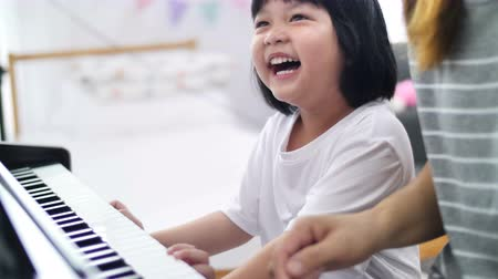 tons : 4K Slow motion little Asian girl playing piano with her mother
