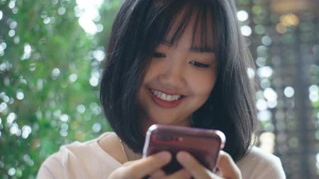 равный : Young Asian woman looking at mobile smartphone