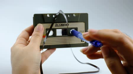 аналог : Women use pen rewind a cassette tape  on white background Стоковые видеозаписи