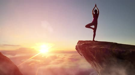 siluety : Woman practices yoga and meditates on the mountain.