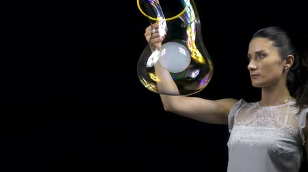 hůlky : Young woman making smoky soap bubble