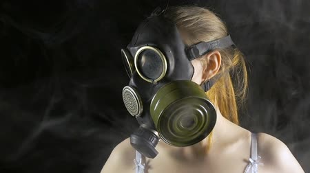 respirator : Young woman in gas mask among smoke