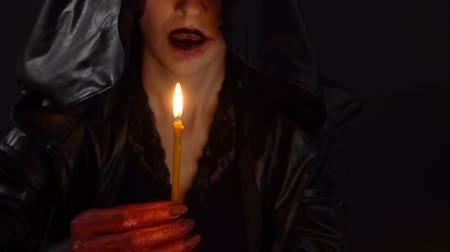 witchcraft : Woman in hood blow out candles