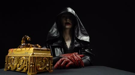 witchcraft : Girl in black hood opening box