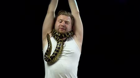 kötés : Tied blond man with anaconda on his neck Stock mozgókép