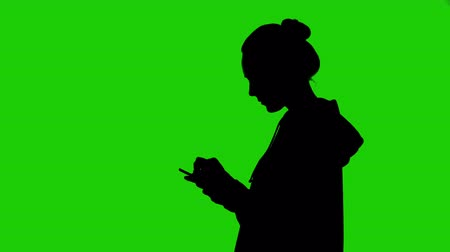 siluety : Girls silhouette with smartphone on green background