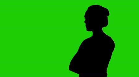 girado : Girls silhouette with arms crossed on green background