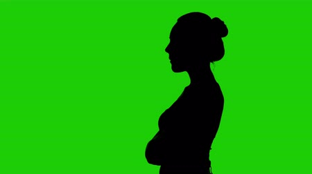 s rukama zkříženýma : Womans silhouette in profile with arms crossed on green background Dostupné videozáznamy