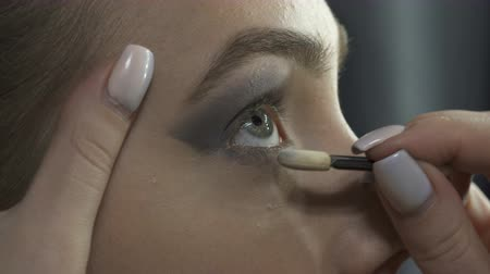 тени для век : Visagist applying eyeshadows in beauty studio