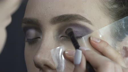 ábrázat : Model during applying dark eyeshadows
