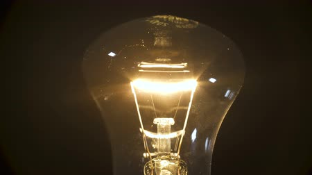 filamento : Video of incandescent bulb on black background Stock Footage