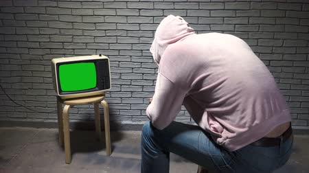 korkunç : Shooting of man in hoodie watching retro tv Stok Video