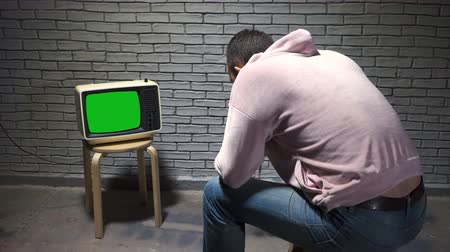 watch tv : Video of man in hoodie watching retro tv