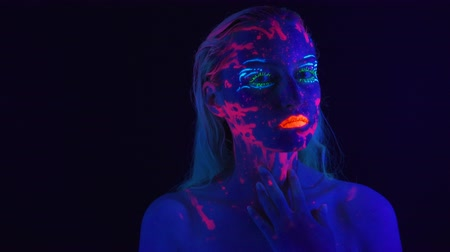 ibolya : Video of young girl with bright bodyart in ultraviolet light