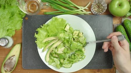 Footage of cooking green salad on black board with vegetables