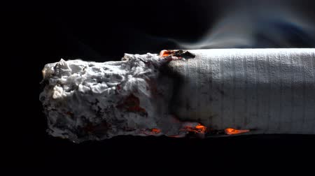 Macro footage of smoldering cigarette on black background