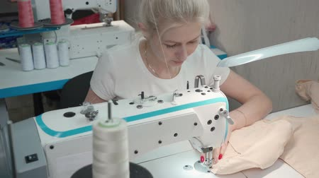 rode draad : Video of young woman sewing dress on electric machine in workshop