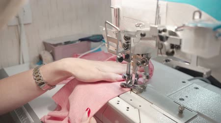 rode draad : Tailor woman sewing pink clothes on electric machine in factory