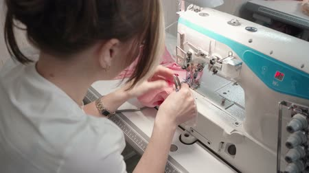 шов : Video of brunette tailor sewing clothes on machine in workplace
