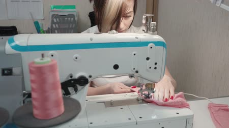 rode draad : Video of tailor sewing clothes on machine in workplace Stockvideo
