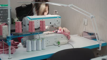 warsztat : Brunette tailor sewing dress on machine in workplace