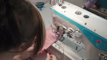 rode draad : Brunette tailor sewing dress on machine in factory