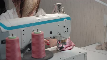 rode draad : Video of brunette tailor sewing order on machine in factory