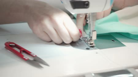 rád : Video of tailor woman sewing label on electric machine