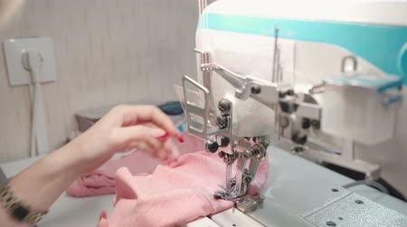 rode draad : Tailor woman sewing pink clothes in factory