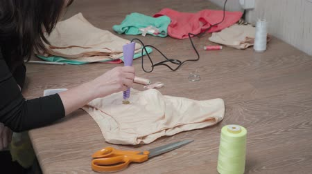 Shooting of tailor gluing pastes on womans panties Stock Footage