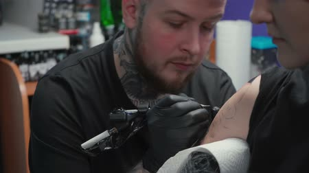 mestre : Footage of doing dark tattoo of snake for woman in studio Vídeos
