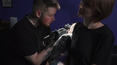 мастер : Shooting of man doing black tattoo of snake for woman