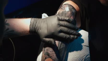inked : Close up video of man doing black tattoo on woman in studio Stock Footage