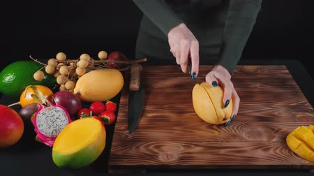 abacate : Video of woman cuts vietnamese mango on wooden board
