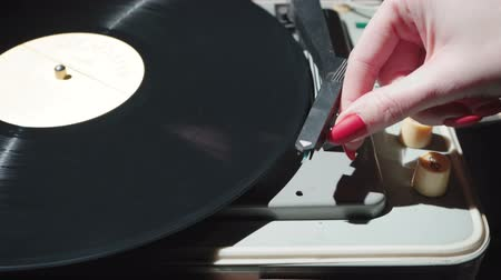 sedmdesátá léta : Footage of woman with red nails turning on retro gramophone