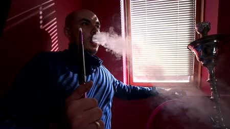 marijuana : Bald man in blue clothes smoking a shisha hookah near the window Stock Footage