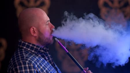 A brutal man with a beard in a plaid blue shirt smoking a water pipe Stok Video