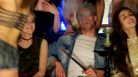 feliz : A young man sits surrounded by girls and smokes a hookah