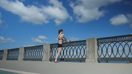 nem városi színhely : Young sporty woman stretching legs along the fence in the morning