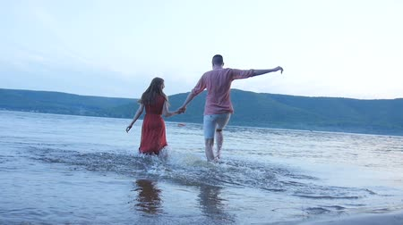 bare foot : The girl and the guy are running into the water