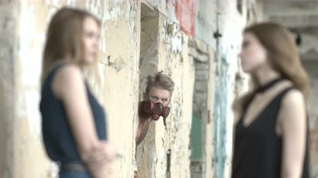 korkunç : Young women talk near an abandoned building and bloody psychopath watches them Stok Video