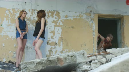 maniac : Girls communicate and a maniac looks out from the doorway of old building
